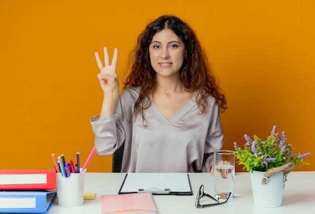 오렌지에 고립 된 세 가지를 보여주는 사무실 도구로 책상에 앉아 웃는 젊은 예쁜 여성 회사원