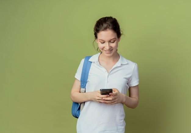 Улыбающаяся молодая симпатичная студентка в задней сумке, использующая свой мобильный телефон, изолирована на оливково-зеленом фоне с копией пространства