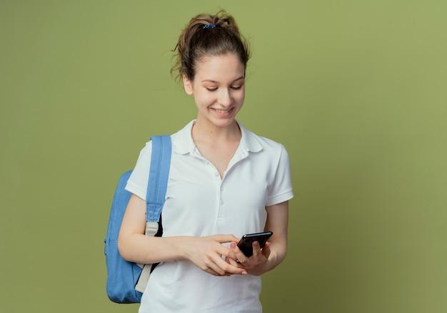 Улыбающаяся молодая симпатичная студентка в сумке на спине с помощью мобильного телефона, изолированного на зеленом фоне с копией пространства