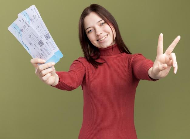 カメラに向かって飛行機のチケットを伸ばす平和のサインをしている若いかわいい女の子の笑顔