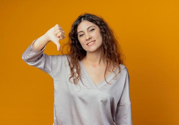 Sorridente giovane ragazza graziosa con il pollice verso il basso isolato sulla parete gialla