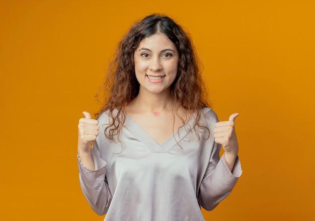 Sorridente giovane bella ragazza con il pollice in alto isolato sulla parete gialla