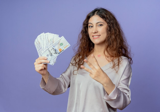 현금을 들고 파란색 벽에 고립 된 세 보여주는 웃는 젊은 예쁜 여자