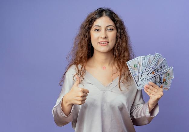 Sorridente giovane ragazza graziosa che tiene contanti e il suo pollice in alto isolato sulla parete blu