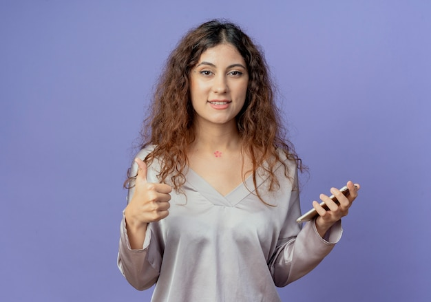 青い壁に分離された彼女の親指を上に携帯電話を保持している若いかわいい女の子の笑顔