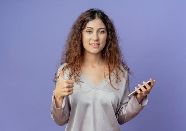 Sorridente giovane ragazza graziosa che tiene il telefono con il pollice in alto isolato sulla parete blu