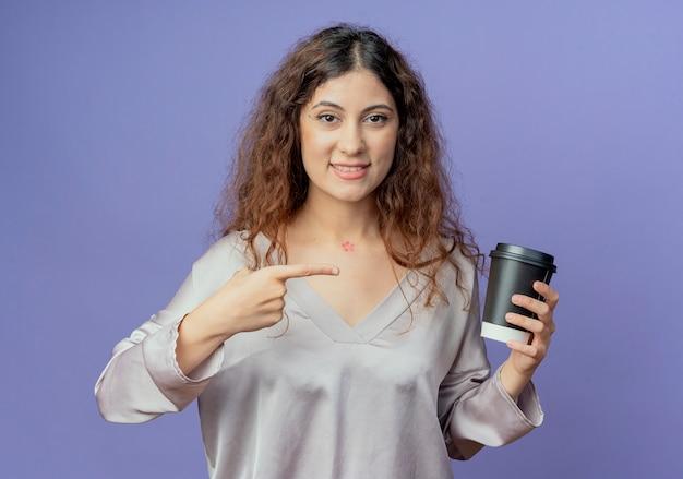 Sorridente giovane ragazza graziosa che tiene e punti alla tazza di caffè isolato sulla parete blu