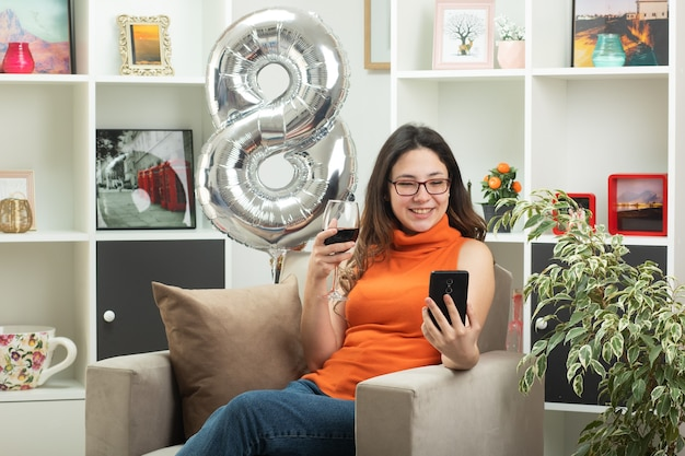 Улыбающаяся молодая красивая девушка в оптических очках держит бокал вина и смотрит на телефон, сидя на кресле в гостиной в международный женский день в марте