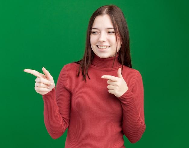 녹색 벽에 격리된 제스처를 하는 쪽을 바라보며 웃고 있는 예쁜 소녀