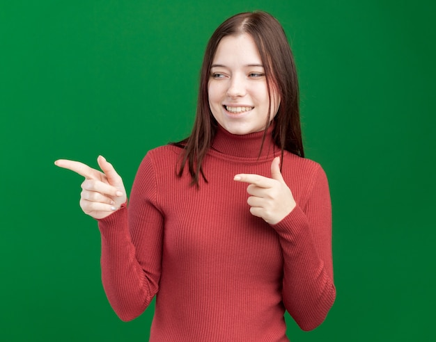 Sorridente ragazza carina che guarda al lato facendoti gesto isolato sul muro verde
