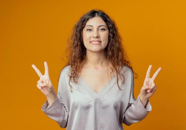 노란색 벽에 고립 된 평화 제스처를 보여주는 웃는 젊은 예쁜 여자