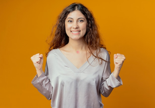 노란색 벽에 고립 예 제스처를 보여주는 웃는 젊은 예쁜 여자
