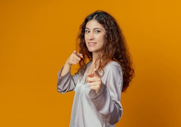 노란색에 고립 된 제스처를 보여주는 웃는 젊은 예쁜 여자