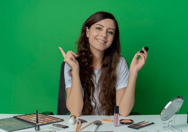 메이크업 도구 메이크업 브러쉬를 들고 녹색 배경에 고립 된 손가락을 올리는 메이크업 테이블에 앉아 웃는 젊은 예쁜 여자