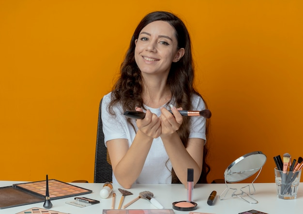 Smiling young pretty girl sitting at makeup table with makeup tools holding powder brush and mascara isolated on orange background