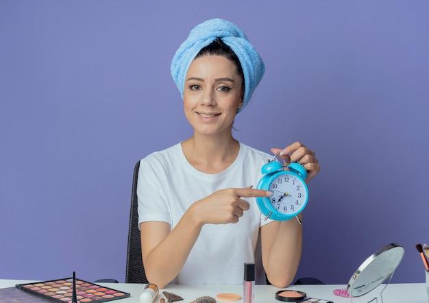 Sorridente giovane bella ragazza seduta al tavolo per il trucco con strumenti per il trucco e con il tovagliolo di bagno sulla testa che tiene e che indica alla sveglia isolata su fondo viola