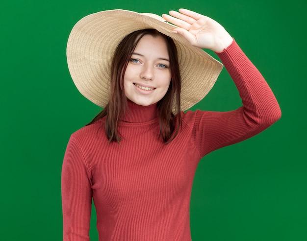緑の壁に分離された帽子をつかむビーチ帽子を身に着けている若いかわいい女の子の笑顔