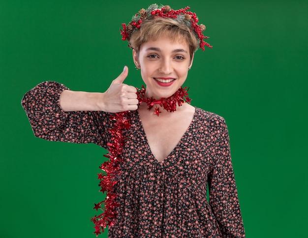 Улыбающаяся молодая симпатичная девушка в рождественском венке и гирлянде из мишуры на шее показывает большой палец вверх изолированной на зеленой стене