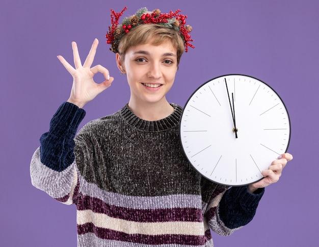 紫色の背景に分離されたokサインをやっているカメラを見て時計を保持しているクリスマスの頭の花輪を身に着けている若いかわいい女の子の笑顔