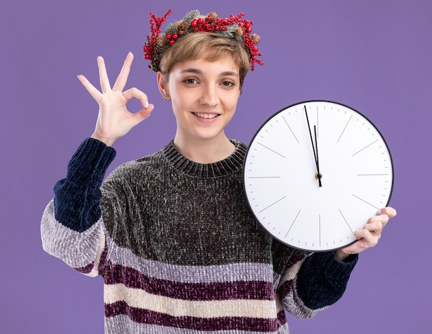 Smiling young pretty girl wearing christmas head wreath holding clock looking at camera doing ok sign isolated on purple background