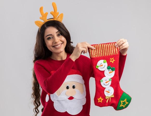 白い壁に隔離のクリスマスの靴下を保持しているトナカイの角のヘッドバンドとサンタクロースのセーターを着て笑顔の若いかわいい女の子