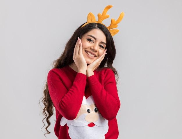 Улыбающаяся молодая красивая девушка в повязке на голову из оленьих рогов и свитере санта-клауса смотрит, держа руки на лице