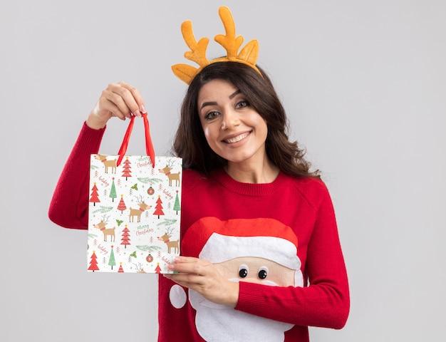Sorridente giovane bella ragazza che indossa la fascia di corna di renna e maglione di babbo natale che tiene il sacchetto del regalo di natale alla ricerca