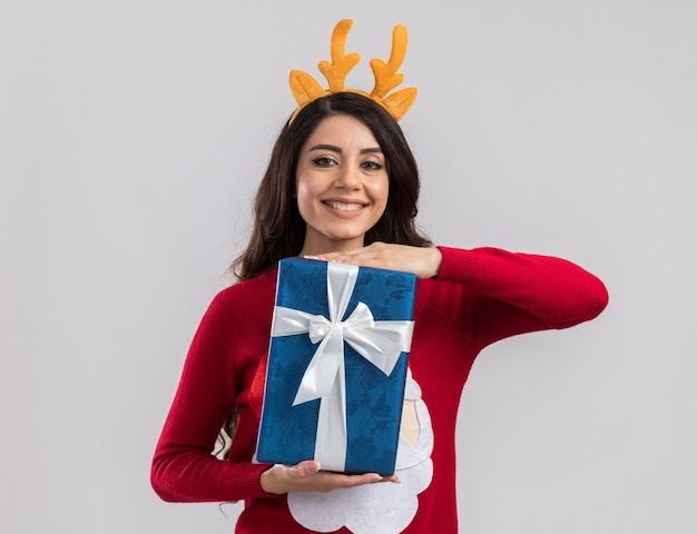 Sorridente giovane ragazza graziosa che indossa la fascia di corna di renna e maglione di babbo natale che tiene il pacchetto regalo di natale alla ricerca