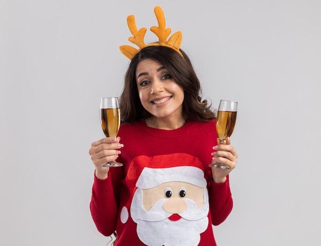 Sorridente giovane bella ragazza che indossa la fascia di corna di renna e maglione di babbo natale con due bicchieri di champagne alla ricerca