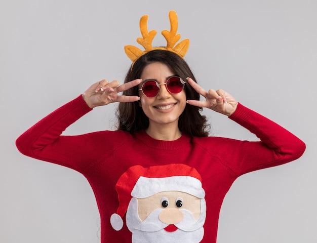 Sorridente giovane bella ragazza che indossa la fascia di corna di renna e maglione di babbo natale con gli occhiali che mostrano i simboli del segno v vicino agli occhi isolati sul muro bianco