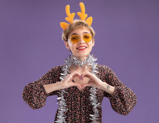 Smiling young pretty girl wearing reindeer antlers headband and tinsel garland around neck with glasses  doing heart sign isolated on purple wall