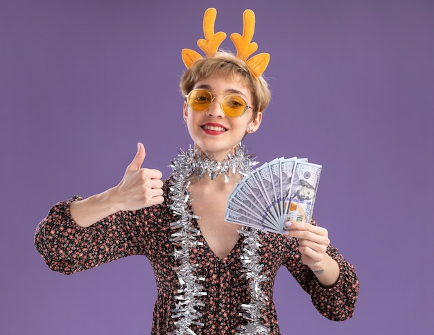 Smiling young pretty girl wearing reindeer antlers headband and tinsel garland around neck with glasses holding money  showing thumb up isolated on purple wall