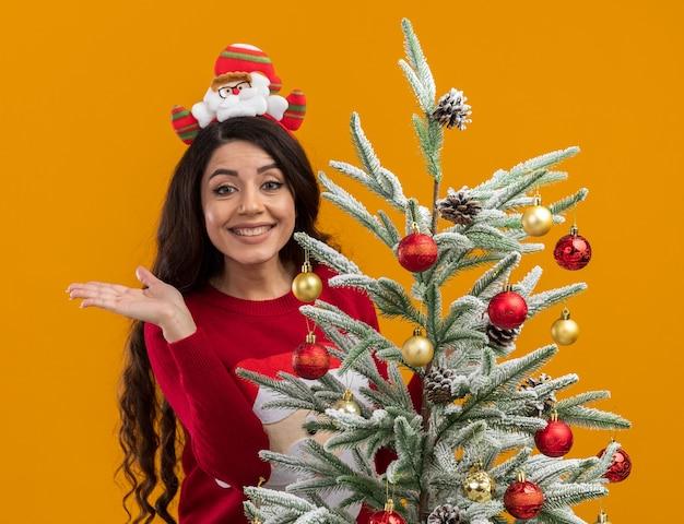 Улыбающаяся молодая красивая девушка в головной повязке санта-клауса и свитере стоит за украшенной елкой, глядя в камеру, показывая пустую руку, изолированную на оранжевом фоне