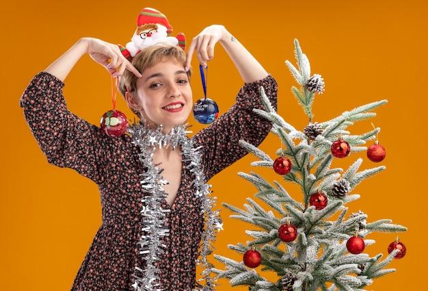 Улыбающаяся молодая красивая девушка с обручем из санта-клауса и гирляндой из мишуры на шее, стоящая возле украшенной елки, держащая рождественскую безделушку возле головы, изолированную на оранжевой стене