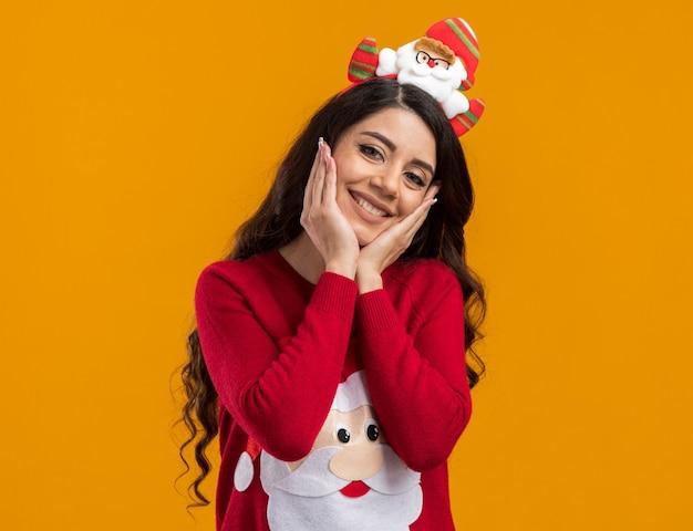 Sorridente ragazza carina che indossa la fascia di babbo natale e un maglione che tiene le mani sul viso isolato sul muro arancione con spazio di copia