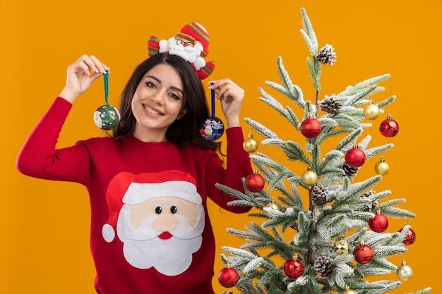 Sorridente ragazza carina che indossa la fascia di babbo natale e maglione in piedi vicino all'albero di natale decorato con palline di natale guardando la fotocamera isolata su sfondo arancione