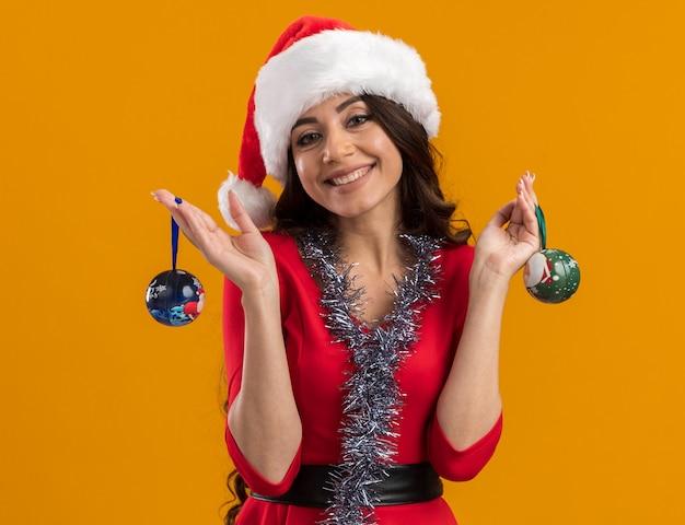 오렌지 벽에 고립 된 크리스마스 싸구려를 들고 목에 산타 모자와 반짝이 갈 랜드를 입고 웃는 젊은 예쁜 여자