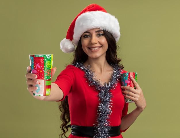 올리브 녹색 벽에 고립 된 하나를 뻗어 크리스마스 커피 컵을 들고 목에 산타 모자와 반짝이 갈 랜드를 입고 웃는 젊은 예쁜 여자