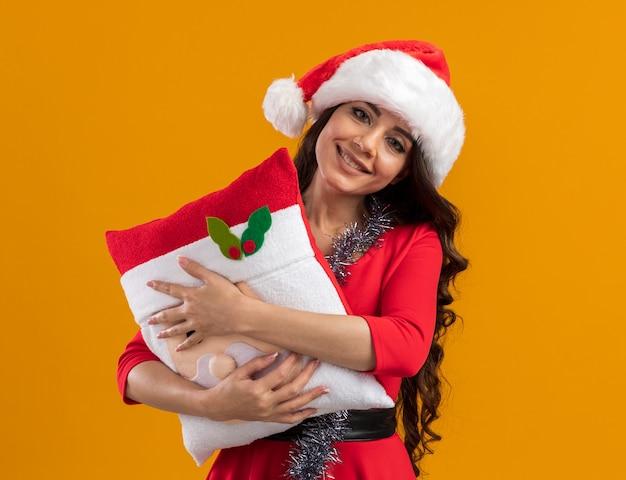 오렌지 벽에 고립 된 산타 클로스 베개를 들고 목에 산타 모자와 반짝이 갈 랜드를 입고 웃는 젊은 예쁜 여자