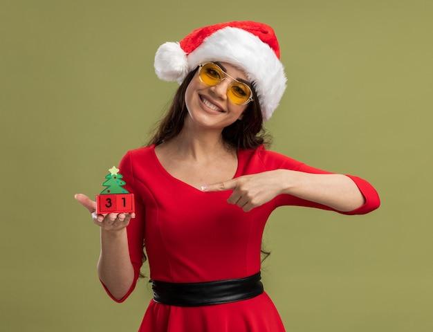 Sorridente ragazza carina che indossa cappello e occhiali da babbo natale che tengono e puntano al giocattolo dell'albero di natale con data isolata su muro verde oliva