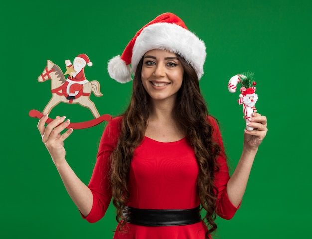 Smiling young pretty girl wearing santa hat holding santa on rocking horse figurine and candy cane ornament looking at camera isolated on green background