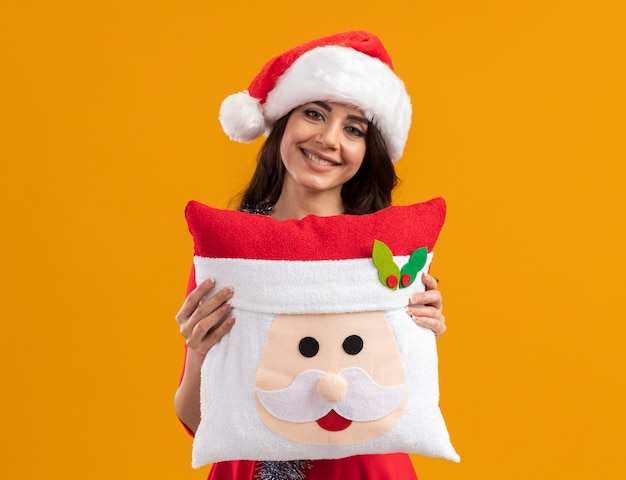 Smiling young pretty girl wearing santa hat and tinsel garland around neck holding santa claus pillow looking