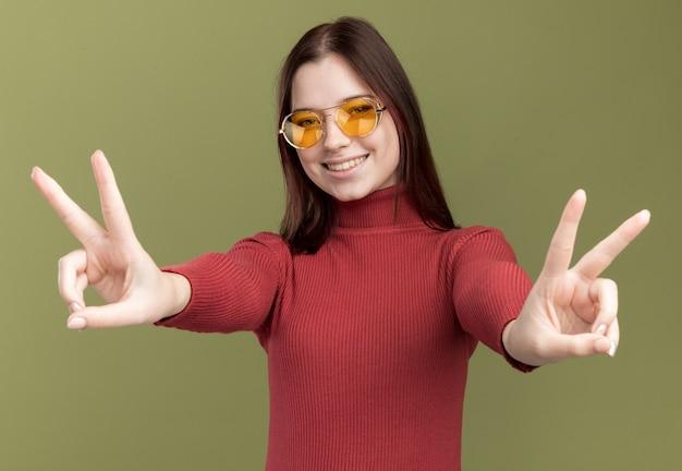 Улыбающаяся молодая красивая девушка в солнцезащитных очках делает знак мира на оливково-зеленой стене