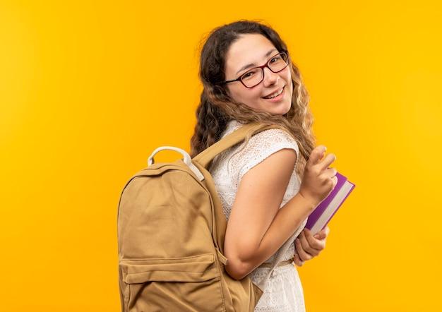Улыбающаяся молодая симпатичная школьница, стоящая в профиль, в очках и задней сумке, держащая книгу, изолирована на желтой стене