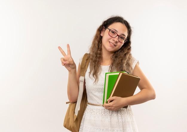 Улыбающаяся молодая симпатичная школьница в очках и задней сумке держит книги, делающие знак мира, изолированные на белой стене