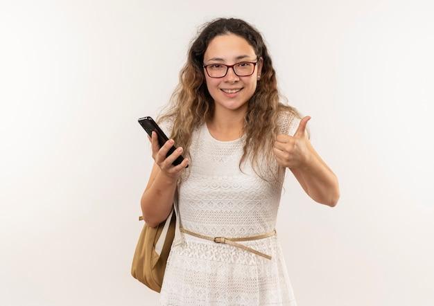 Улыбающаяся молодая симпатичная школьница в очках и задней сумке держит мобильный телефон и показывает большой палец вверх изолированной на стене