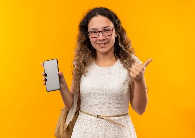 Улыбающаяся молодая симпатичная школьница в очках и задней сумке показывает мобильный телефон и большой палец вверх изолирована на желтой стене