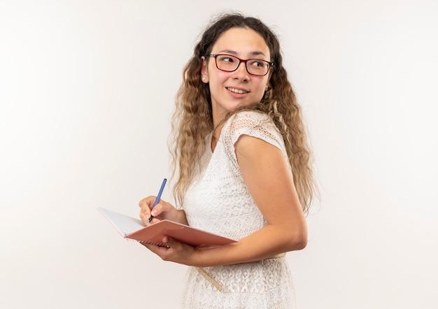 Улыбающаяся молодая симпатичная школьница в очках и задней сумке, стоящая в профиле, глядя за письмом ручкой на блокноте, изолированном на белой стене