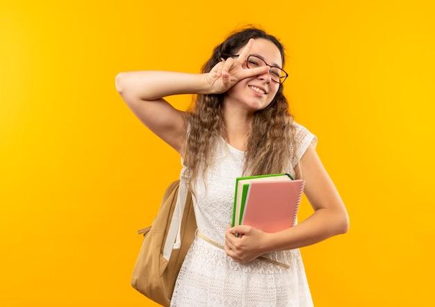 Sorridente giovane studentessa graziosa con gli occhiali e borsa posteriore che tiene il libro e il blocco note facendo segno di pace isolato sulla parete gialla