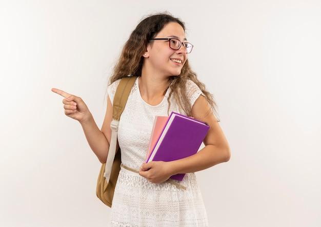 Sorridente giovane studentessa graziosa con gli occhiali e borsa posteriore che tiene il libro e il blocco note che punta e che esamina il lato isolato sul muro bianco